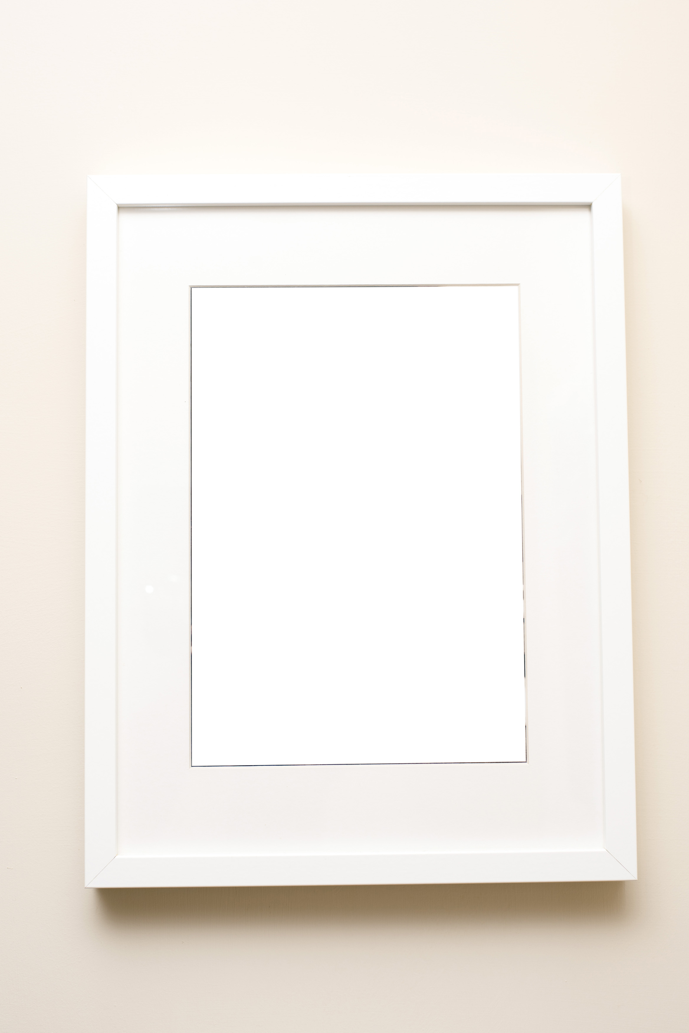 Free image of Blank picture frame in white over wall