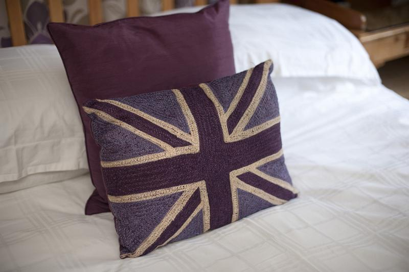 Patriotic British themed bedroom with cushions bearing the Union Jack flag on the bed on white linen, close up view
