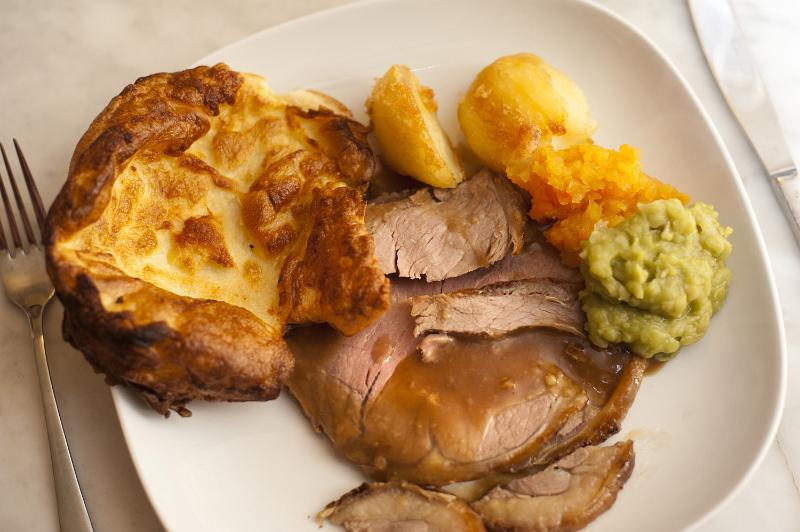Traditional English roast beef dinner served with Yorkshire Pudding, vegetables and a rich gravy