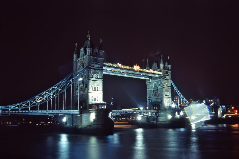 View across the River Thames of the historic Tower Bridge, London illuminated at night and reflected in the water below