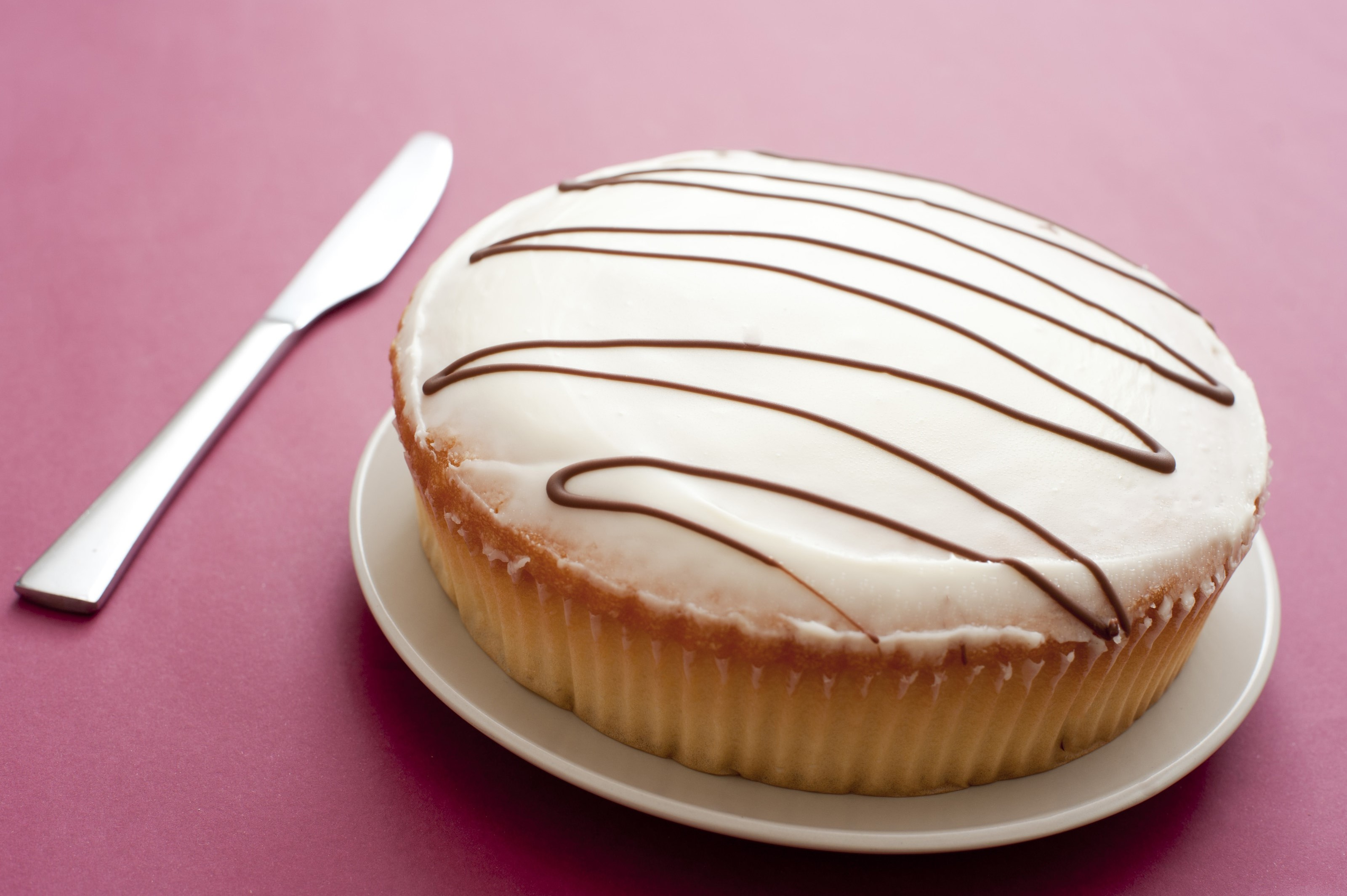 & Free image of Large Iced Cup Cake on Plate with Knife