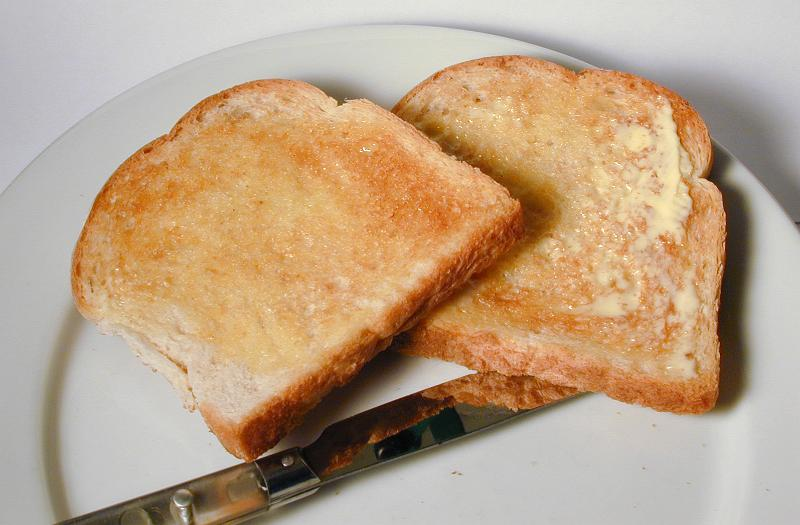 Free Stock Photo: Two slices of hot buttered white toast for breakfast served with a knife on a side plate as an accompaniment to the meal
