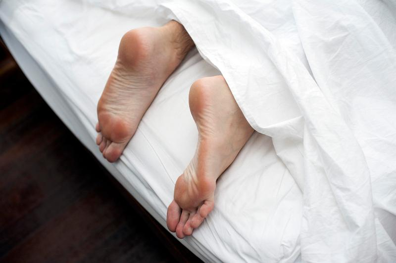 Free Stock Photo: Man lying in bed on a lazy day with his feet sticking out the bottom of the bed from under the white bedclothes, close up view