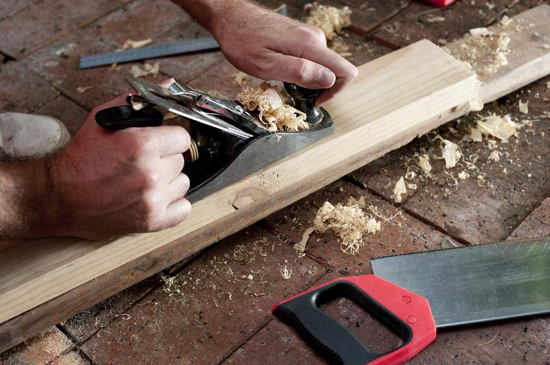 Man planing a length of wood by hand using a handheld plane with an adjustable blade in a DIY and renovation concept