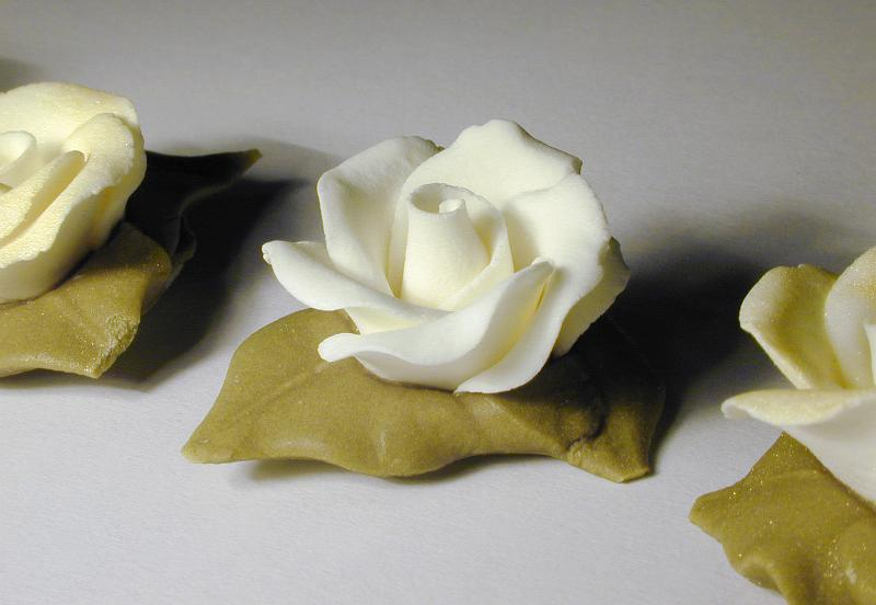 Free image of Row of White Icing Roses with Leaves