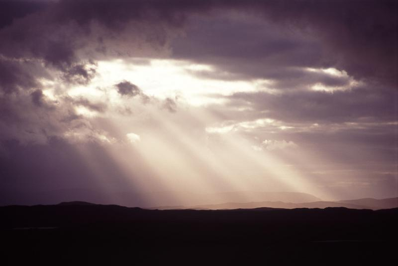 Sunbeams shining through a hole in the dense cloud cover in a stormy grey sky throwing diagonal rays onto the silhouetted hills below