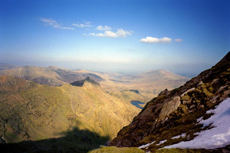 View from a summit with a pocket of late snow of a Welsh mountain landscape with peaks disappearing into the distance on a clear sunny blue sky day
