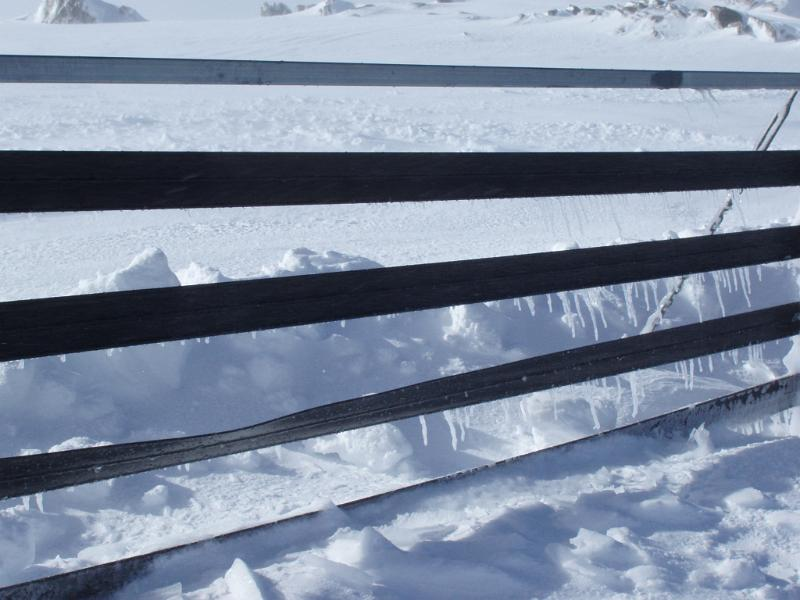 icicles forming on a mountain top snowdrift fence