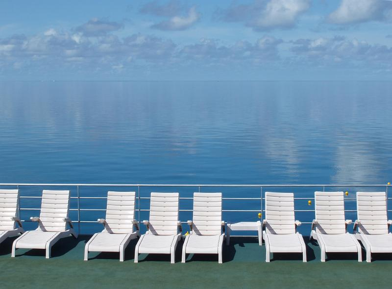 a line of sun loungers and still blue water, great barrier reef, australia