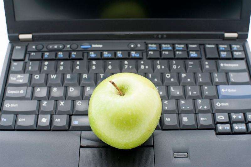 Education comcept: Green apple above black keyboard laptop personal computer.