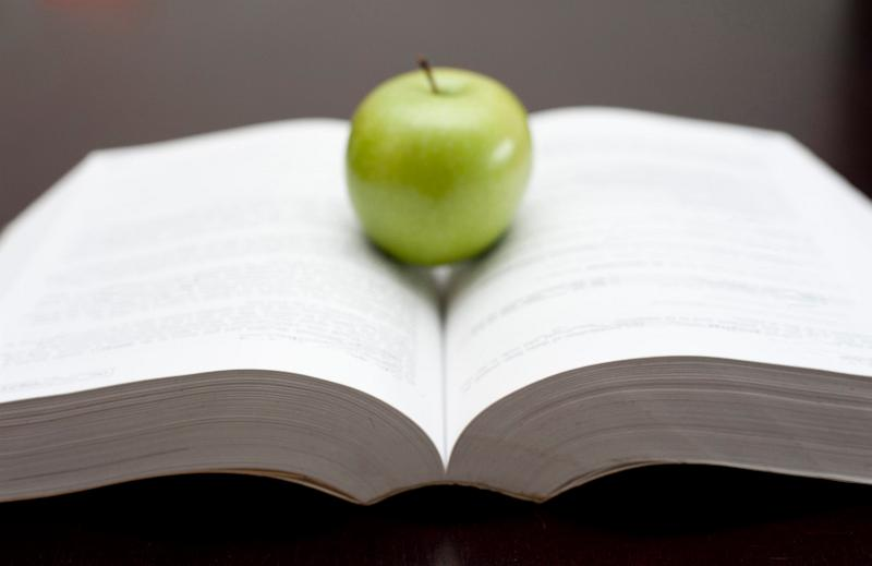 Fresh green apple balanced on the open pages of a textbook or novel in an education and learning or relaxation and reading concept