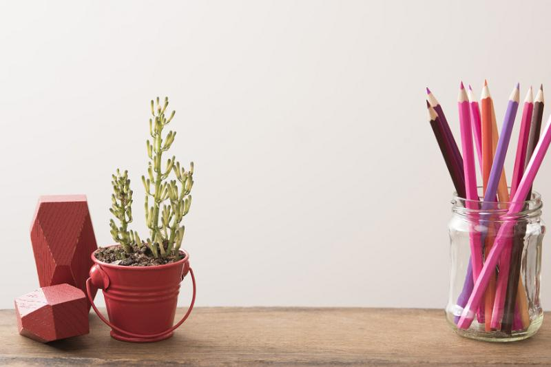 Free Stock Photo: Plant growing in short red pail on wood table beside mason jar filled with colored pencils