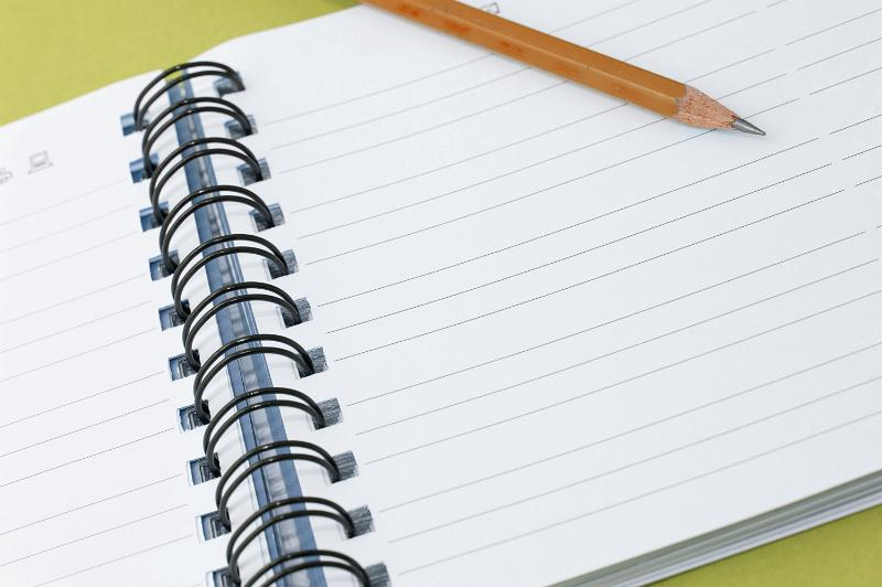 Blank spiral ringbound notebook with ruled pages and a sharpened wooden pencil with room for your text or message